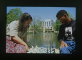 [Students playing chess near pond and library]