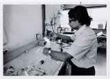 [Researcher working on glassware in biology lab]