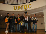 [2008 Chess Team with trophy, True Grit, and a UMBC cheerleader]