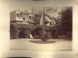 [Woman sitting in front of large house with awning]