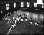 [Boys' Latin School students performing drills with flags in gym]
