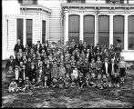 [Group portrait of children in front of a school]