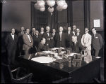 [Group portrait of men around desk]