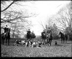 [Men on horses with hounds at hunt club]