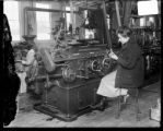 [Woman working at metal lathe]