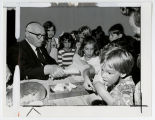 [Louis Kaplan distributing apple slices to children of Beth Am congregation for Rosh Hashanah,...