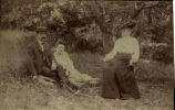 [Man and woman sitting on grass and women seated in chair]
